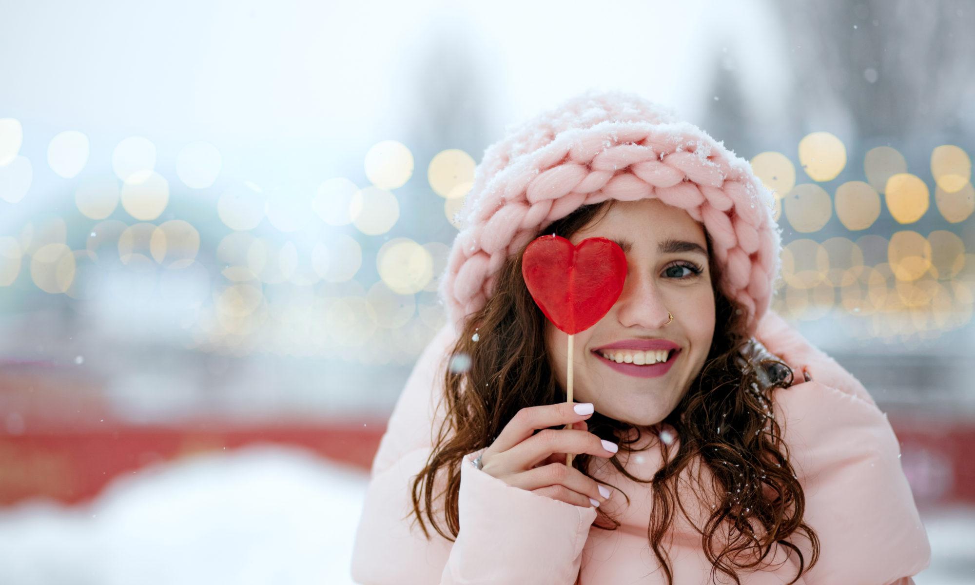 Dziewczyna w różowym stroju zimowym z lizakiem w kształcie serca przy oku