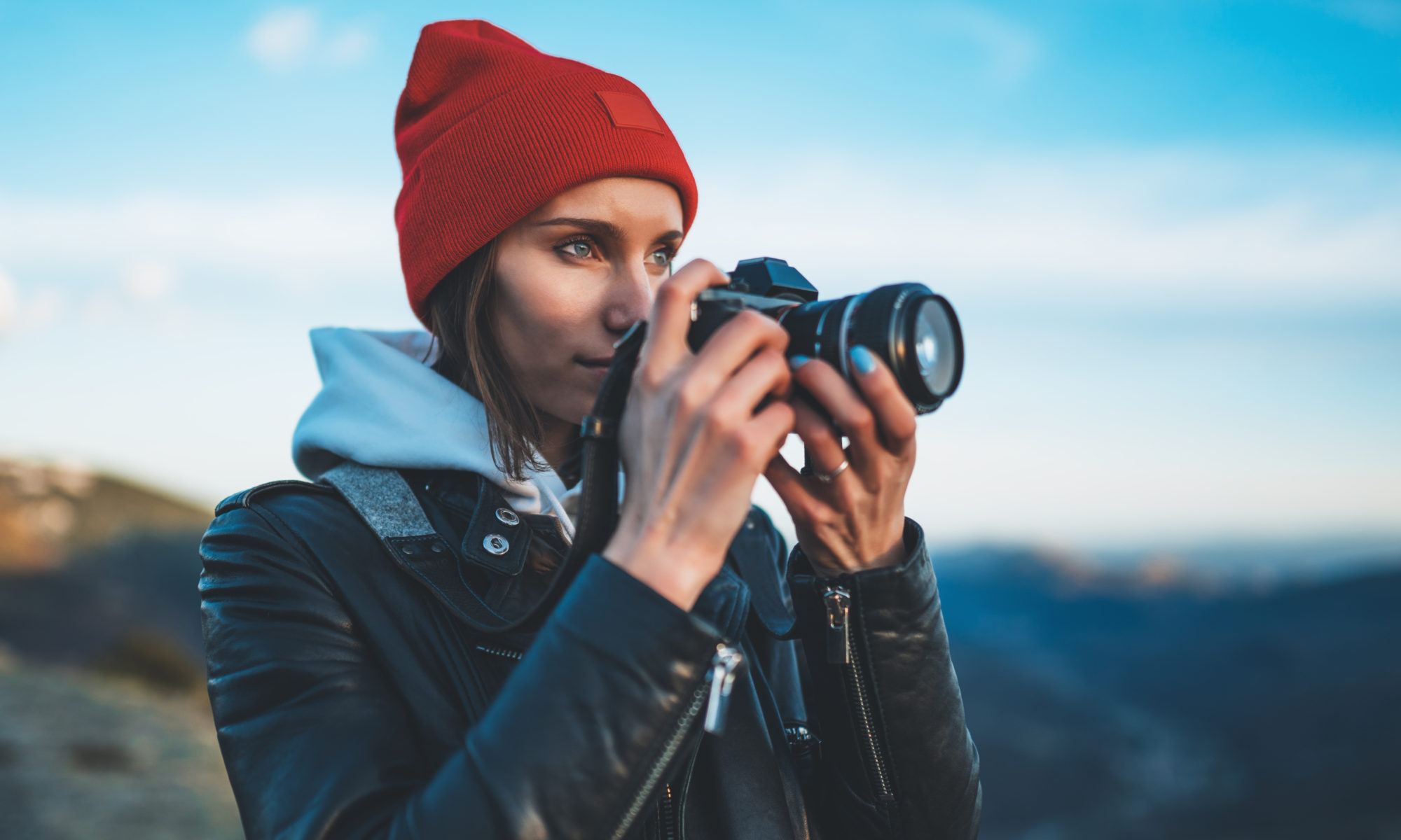 Dziewczyna w czerwonej czapce robiąca zdjęcie