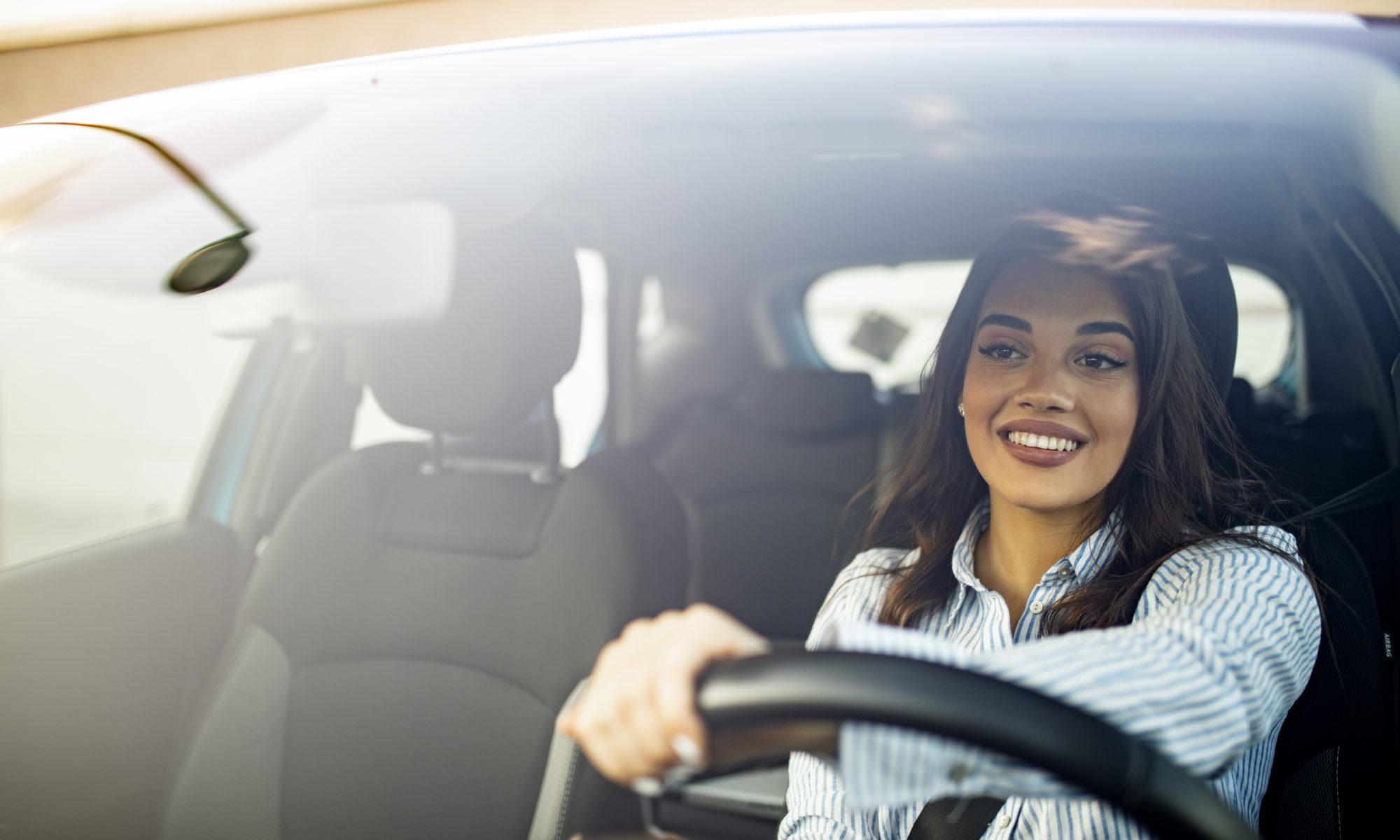 Piękna młoda kobieta za kierownicą samochodu