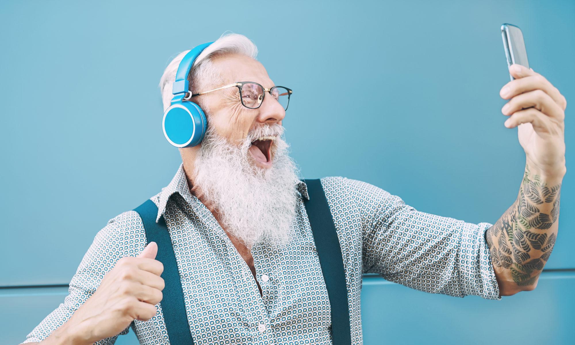 Starszy człowiek z brodą i tatuażem i błękitnymi słuchawkami na uszach