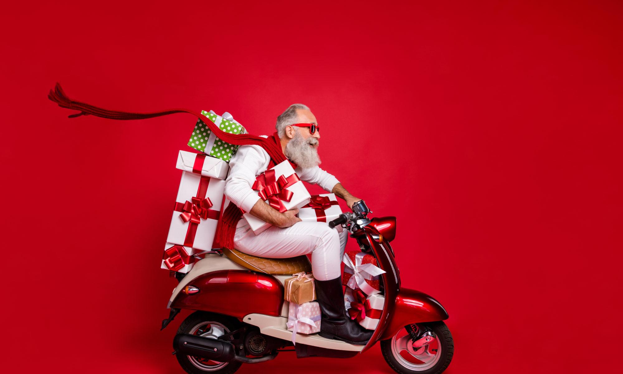 Nowoczesny święty Mikołaj z prezentami na skuterze