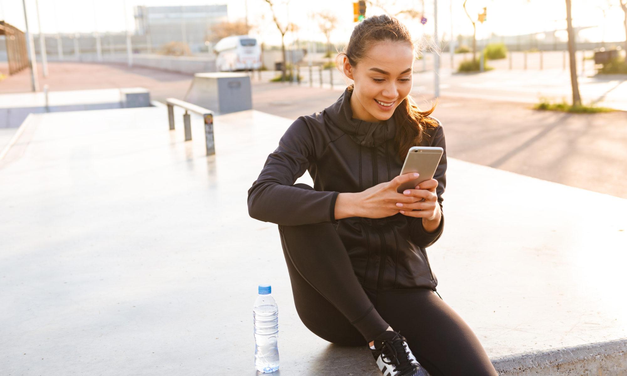 dziewczyna w stroju sportowym ze smartfonem w ręku