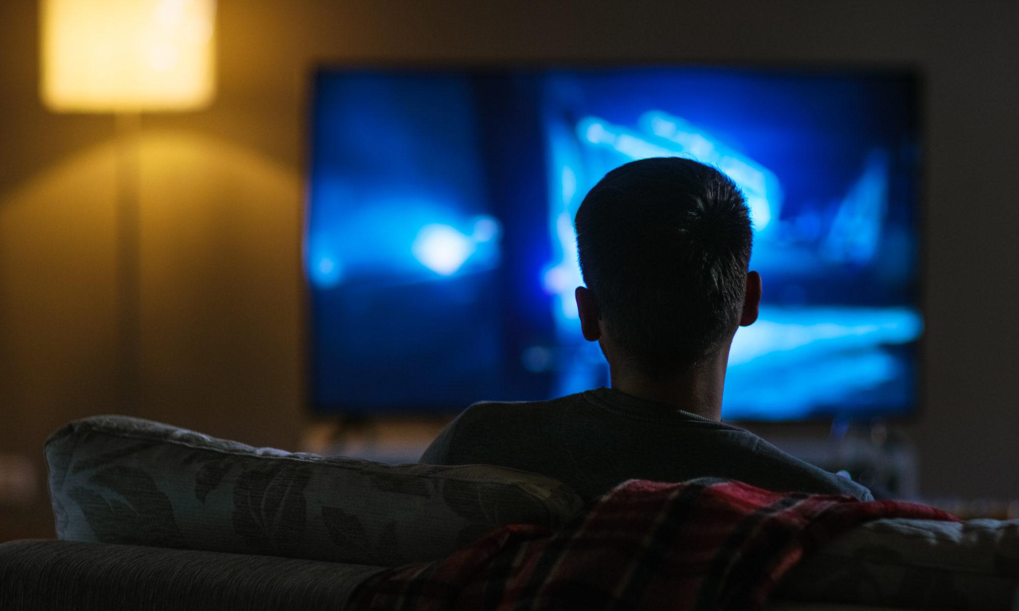 mężczyzna oglądający telewizję nocą