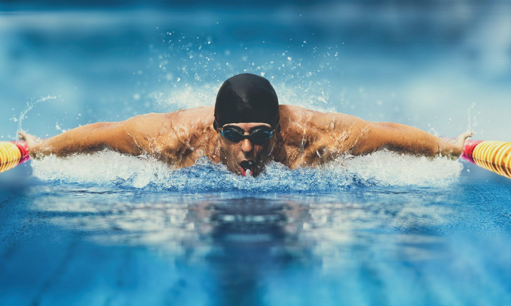 mężczyzna płynący w basenie stylem motylkowym