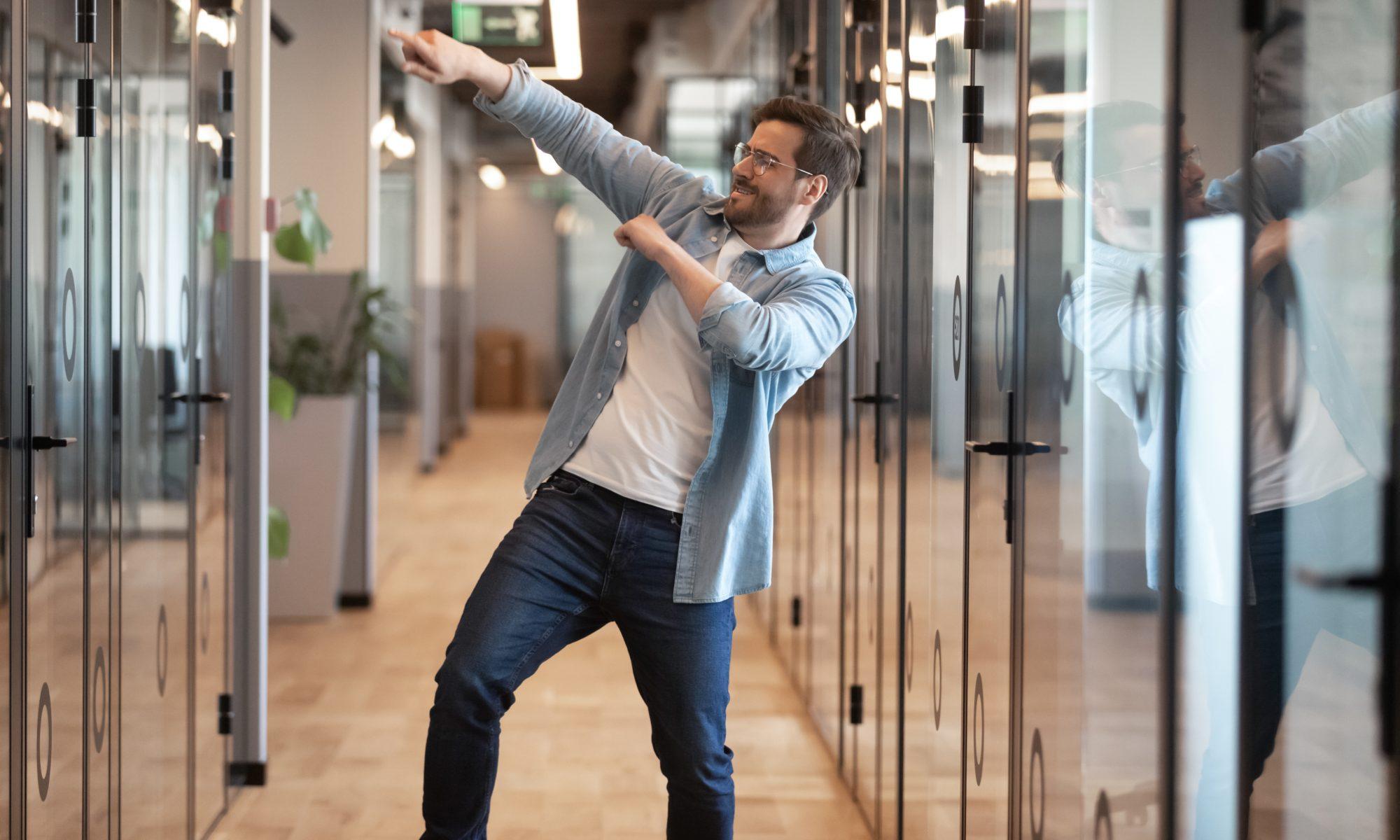 mężczyzna tańczący z radości w biurze