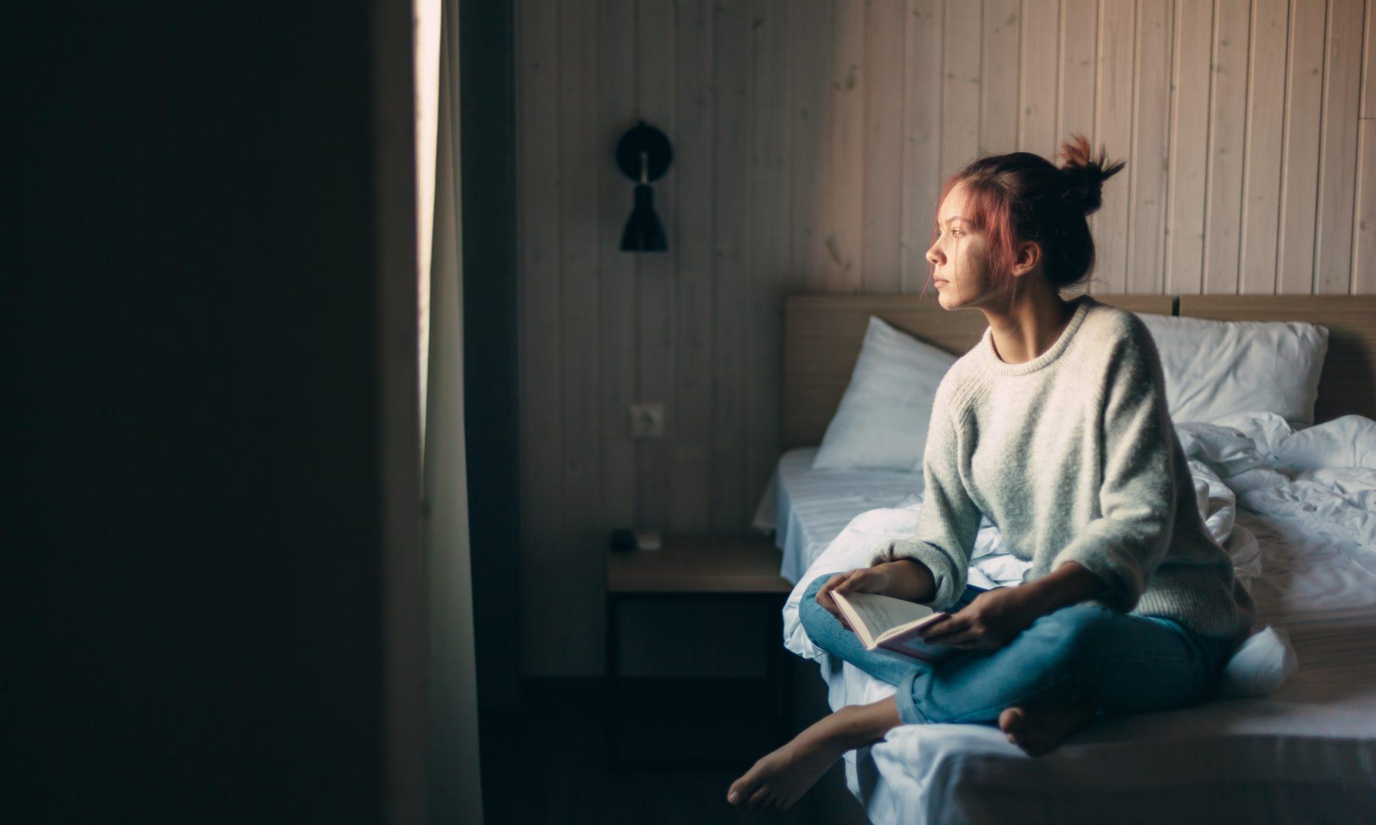 dziewczyna z książką patrząca w okno