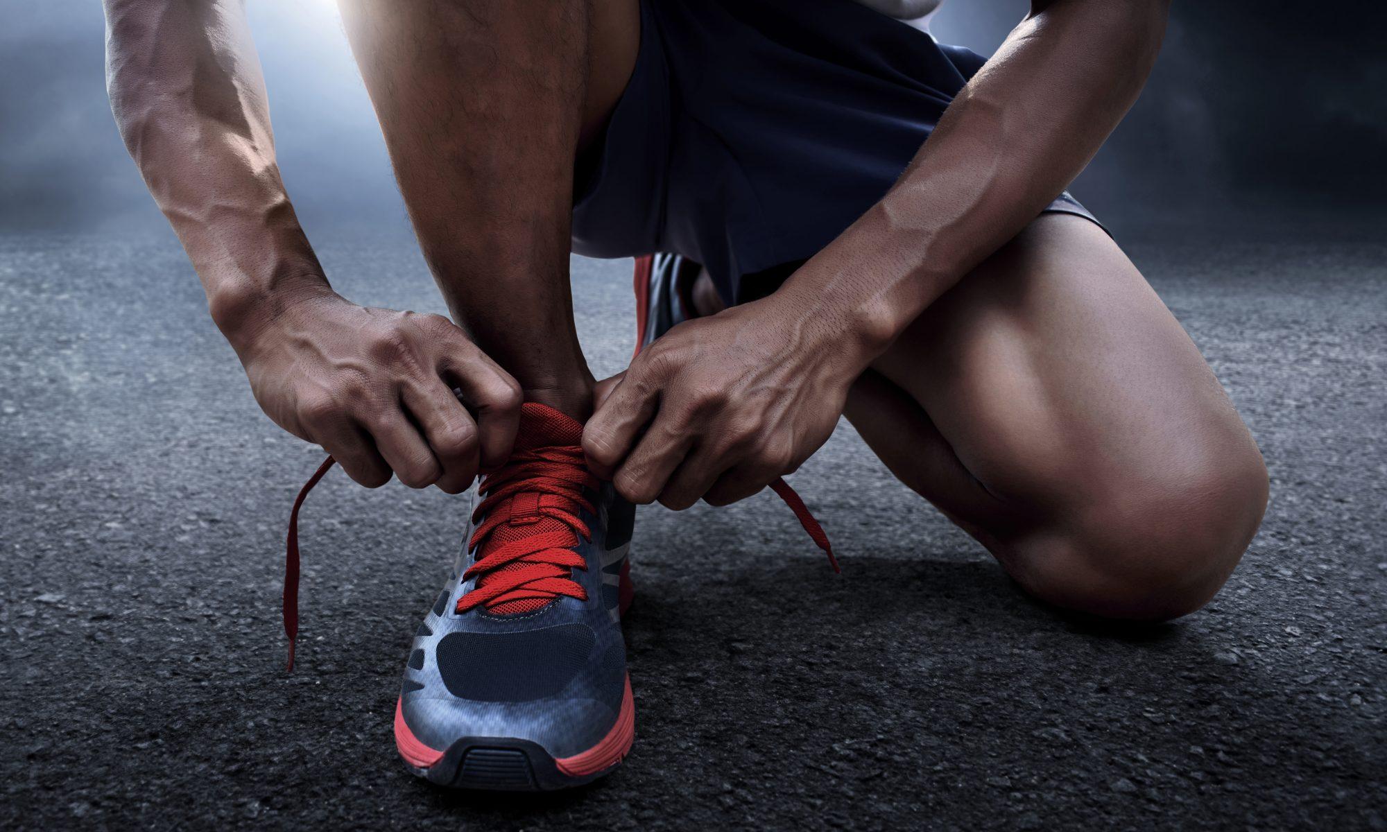 mężczyzna zawiązujący buty do biegania